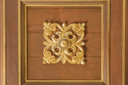 moldings: Detail view of elegant wood interior roof with moldings and iron floral ornament at center.