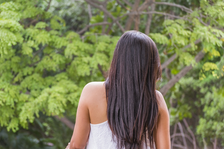 elegantly: Back view of young adult woman elegantly dressed against forest background