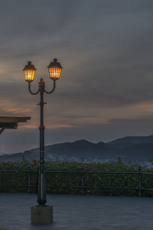 guayaquil: Sunset scene with antique lamp as the main subject and mountains at background in Cerro del Carmen, Guayaquil, Ecuador Stock Photo