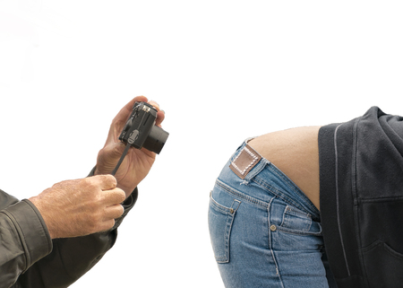 photo montage: Funny photo montage of old man taking photos of crouching young woman wearing jeans against white background