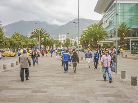 walking zone: QUITO, ECUADOR, OCTOBER - 2015 - People walking at sidewalk with mountains at background in a modern downtown zone of Quito, Ecuador