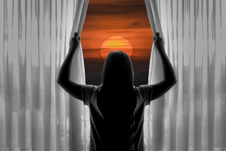 woman looking up: Back view of silhouette of young woman opening curtains against sunset background. Stock Photo