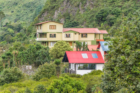 highs: Aerial view of a group of houses and buildings located in valley surrounded by leafy mountains in Banos, Ecuador