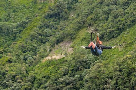 highs: Person making canopy, and extreme touristic activity hanged on wire at highs in Banos, Ecuador