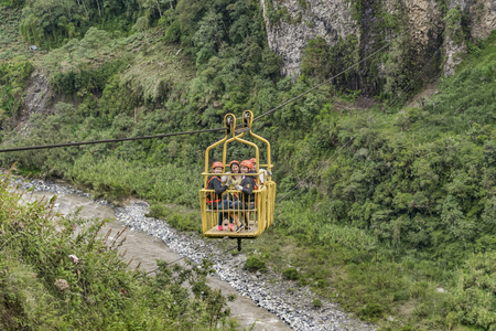 highs: BANOS, ECUADOR, OCTOBER - 2015 - Group of people enjoying an extreme trip at highs of mountains hanged on a cableway in Banos, Ecuador. Editorial