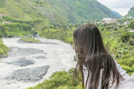 back straight: Back view of adult young woman with black straight hair contemplating the landscape of in Banos, Ecuador Stock Photo