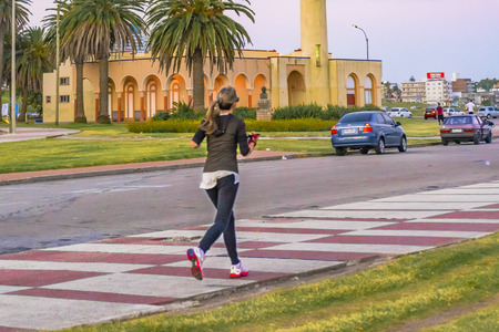 montevideo: MONTEVIDEO, URUGUAY, DECEMBER - 2015 - Adult blonde woman with sports wear running at sidewalk in Montevideo, Uruguay Editorial