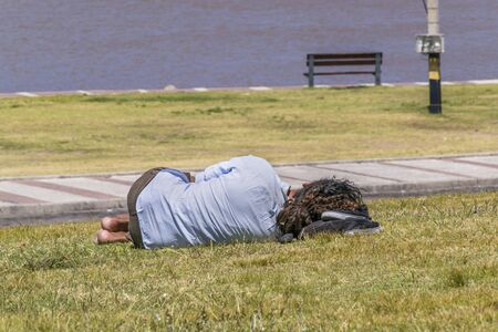 indigent: Back view of indigent sleeping at grass in Park Stock Photo