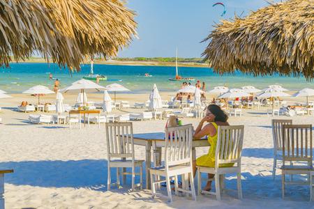 lonley: JERICOACOARA, BRAZIL, DECEMBER - 2015 - Adult woman sit lonley at outdoor restaurant in Lagoa do Paraiso beach in Jericoacoara Brazil Editorial