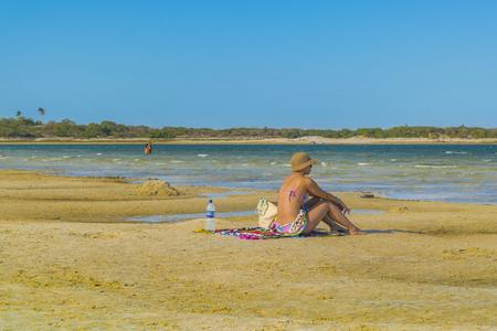 lonley: JERICOACOARA, BRAZIL, DECEMBER - 2015 - Adult woman sit lonely at Lagoa do Paraiso beach in Jericoacoara Brazil