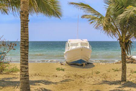 aground: White yatch aground at empty beach in Puerto Lopez town, Ecuador, South America Stock Photo