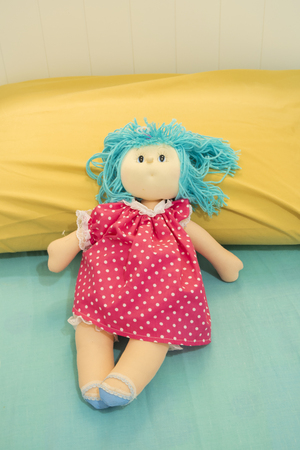 Top view shot of cute dresses girl doll sitting at bed