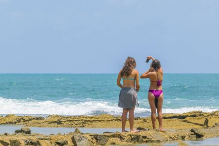 Two young women at rocky coast in Natal, Brazil