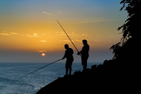Collage technique of two adult men fishing at shore against sunset sky background