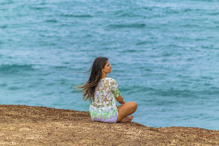 PIPA, BRAZIL, JANUARY - 2016 - Young attractive woman sitting at edge of rocky hill with the ocean at the background in Pipa, Brazil