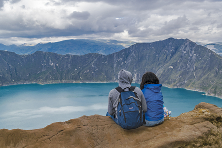 Couple sitting at rock watching the view at Quilotoa lake, Ecuador