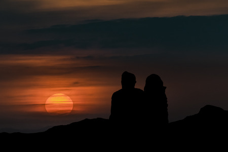 highs: Silhouette illustration of couple sitting at highs watching the view
