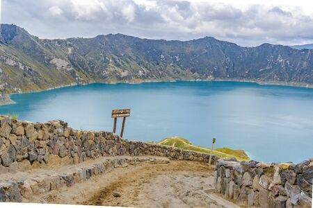 crater lake: Quilotoa lake and andes range mountain against overcast cloudy background landscape scene, Ecuador