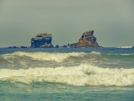 Seaside landscape scene with two big rocks in the middle of the ocean at ecuadorian coast. Stock Photo