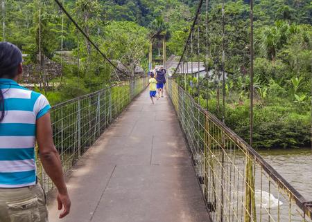 PUYO, ECUADOR, OCTOBER - 2015 - Children running at bridge at ecuadorian side of amazonia in Puyo district, Ecuador