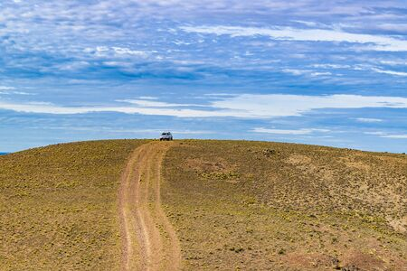 Van parked at top of hill at arid landscape environment located in the argentinian patagonian in Santa Cruz province, Argentina