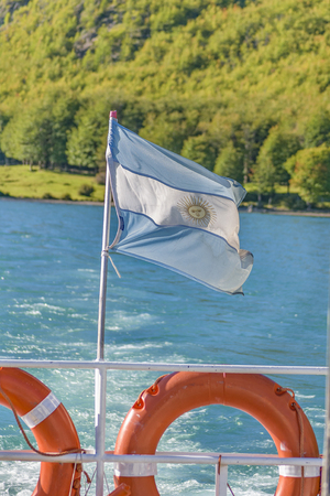 Argentinian flag fluttering at back of boat.Patagonia, Argentina 写真素材