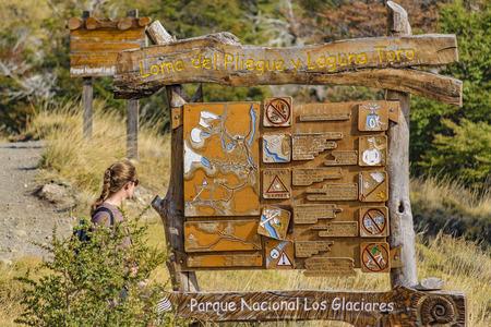 SANTA CRUZ, ARGENTINA, MARCH - 2016 - Young blonde women watching post information about trekking roads at El Chalten. Patagonia - Argentina