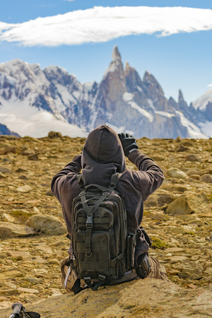 Back view of adult man sitting at rock taking photos of mountains at end of one of trekkin road of El Chalten. Patagonia, Argentina