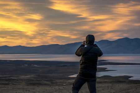 Back view of adult man taking photos of vendimia lake and andes mountains at Mirador de las aguilas viewpoint.El Chalten, Patagonia, Argentina Stock Photo