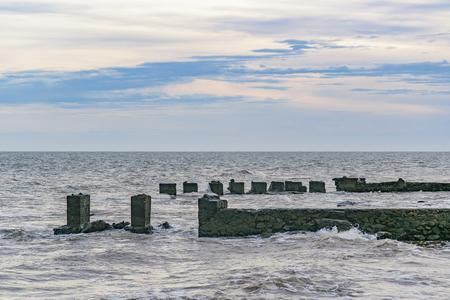 Seascape scene met gebroken golfbreker bij de rivier. Stockfoto