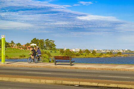 MONTEVIDEO, URUGUAY, ENERO - 2016 - Hombres que montan una bicicleta en la acera en el paseo marítimo en la ciudad de Montevideo, Uruguay