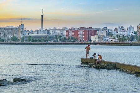 MONTEVIDEO, URUGUAY, FEBRUARY - 2016 - People fishing at breakwater at coast of Montevideo city, Uruguay