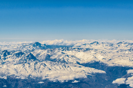 Aerial view from window plane of andes range mountains over chilean territory.