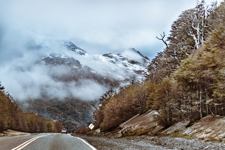 Highway surrounded by forest and snowy mountain at chilean patagonian territory