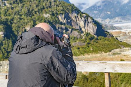 Side view man taking photos at exploradores glacier viewpoint, Aysen, Chile