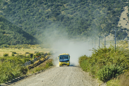 AYSEN, CHILE, APRIL - 2017 - Tourist bus driving at gravel road at austral route in patagonia, chile