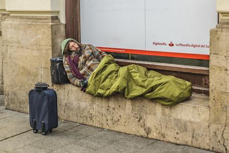MADRID, SPAIN, DECEMBER - 2017 - Adult woman sleeping at street in Madrid city, Spain Editorial