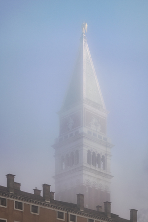 VENICE, ITALY, JANUARY - 2018 - Foggy winter scene at piazza san marcos with campanille tower as main subject at venice city, Italy