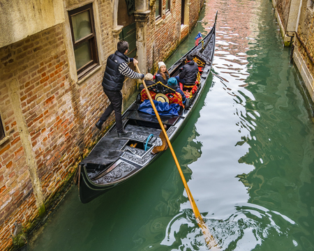 VENICE, ITALY, JANUARY - 2018 - Gondolier taking tourist at small canal in venice city, Italy 에디토리얼