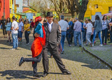 BUENOS AIRES, ARGENTINA, SEPTEMBER - 2018 - Couple of tango dancer posing for a photo at traditional caminito street at la boca neighborhood, Buenos Aires