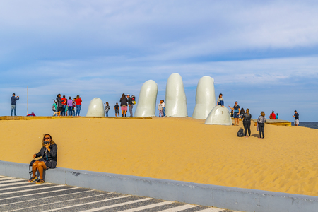 PUNTA DEL ESTE, URUGUAY, OCTOBER - 2018 -  Tourist at most famous landmark monument located at la brava beach in punta del este city, Uruguay