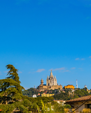 Blue sky surrounded by trees and sacred jesus temple at distant in tibidabo park, Barcelona, Spain