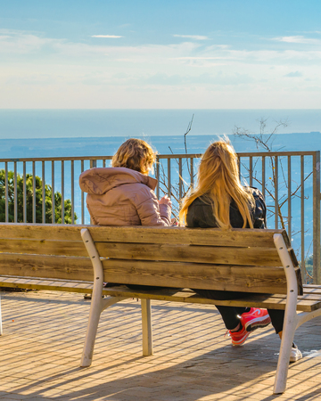 Two young blond women sitting at chair watching the view at tibidabo park in Barcelona