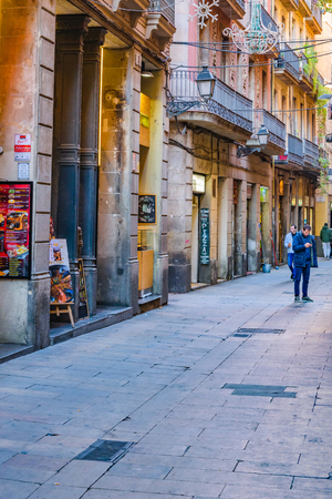 BARCELONA, SPAIN, JANUARY - 2018 - Narrow street surrounded by medieval buildings at gothic district in barcelona city, spain