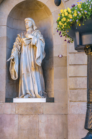 Stone sculpture of religious man with cassock at exterior niche of old building at gothic district in barcelona city, spain. Stockfoto