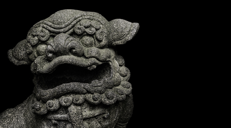 Mythologic chinese stone lion sculpture head isolated on black background