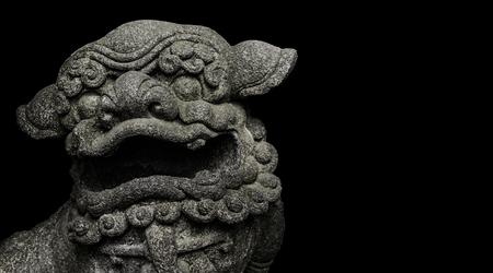 Mythologic chinese stone lion sculpture head isolated on black background