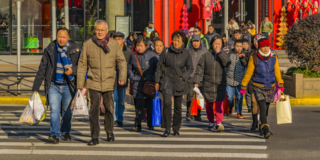 SHANGHAI, CHINA, DECEMBER - 2018 - Winter urban day scene people crossing street at people square zone in shanghai city, china Editorial