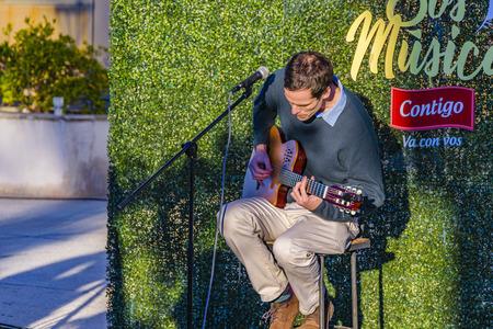 MONTEVIDEO, URUGUAY, JUNE - 2019 - Man playing guitar at outdoor street fair at carrasco neighborhood, montevideo city, uruguay