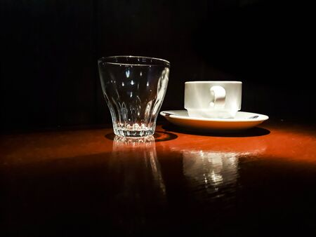 High contrast low light interior bar scene depicting a white coffee cup and small glass cup over table